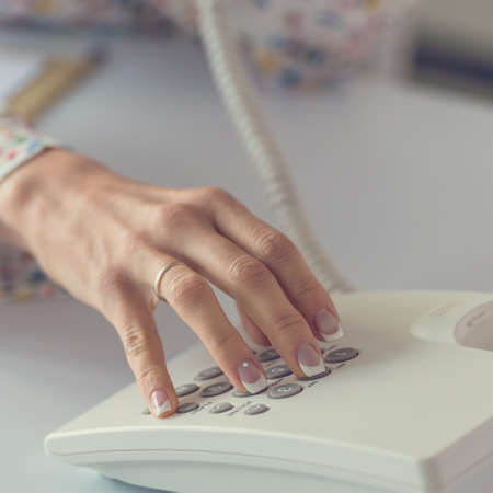 Closeup view of female hand dialing a telephone number using white landline phone. Stock fotó