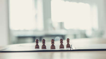 Five pawn chess figures standing on an application form or document in a folder in a conceptual image. Stockfoto - 120899520
