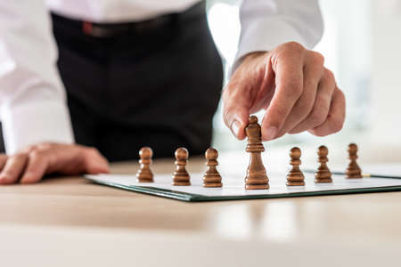 Business employer holding chess figure of king in front of pawn figures in a conceptual image.