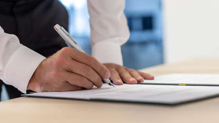 Business executive signing a document or contract using ink pen. Stock Photo