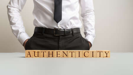 Word Authenticity spelled on desk with wooden cubes with businessman standing in background.