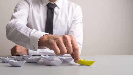 Business executive pushing forward first of many paper made origami boats that also stands out by yellow colour. Stock Photo