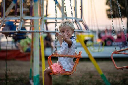 Joyeux enfant blond en bas âge saluant la caméra alors qu'il monte sur un carrousel dans un parc d'attractions au bord de la mer.