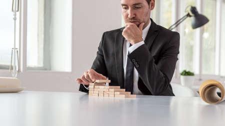 Ernsthafter nachdenklicher Geschäftsmann, der an seinem Schreibtisch sitzt und eine Treppe aus Holzpflöcken in einem konzeptionellen Bild von Geschäftsvision und Ehrgeiz zusammenbaut.