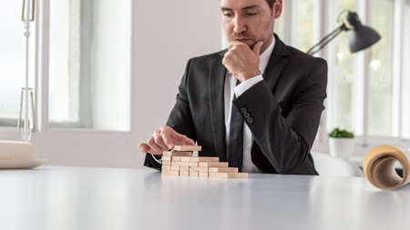 Serious thoughtful businessman sitting at his office desk assembling a staircase of wooden pegs in a conceptual image of business vision and ambition.