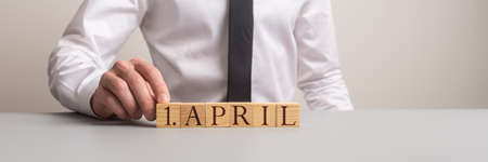 Wide view image of a man assembling an 1.April sign of wooden cubes. Stock Photo