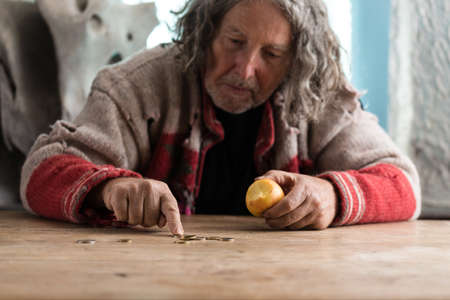 Senior homeless man in torn sweater eating old apple and counting Euro coins on an old wooden desk.