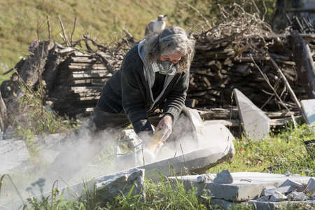A sculptor working outside wearing protective mask as he shapes a large piece of stone using a grinding machine. Stock Photo