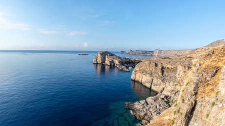 View of beautiful rocky cliffs of the island of Rhodes steeping in to blue see.