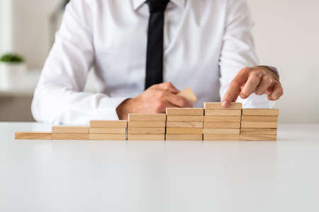 Businessman making stairs of wooden pegs in a conceptual image of business vision and promotion.