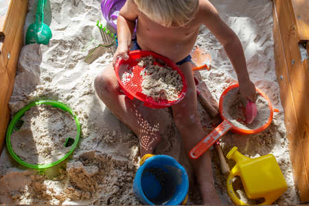 Top view of toddler boy playing in sand with his toys on a hot summer day. Stock Photo