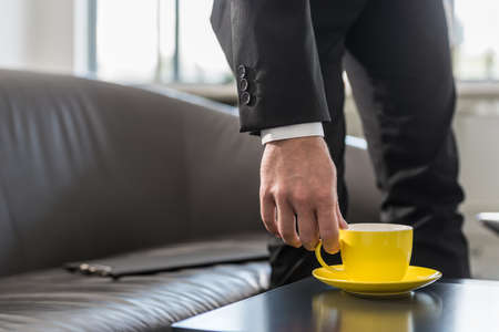 Businessman on a break in his office leaning down toward coffee table to pick up coffee mug as he rest his documents on the couch. Stock Photo