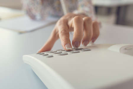 Closeup view of female receptionist dialing a telephone number using white landline phone.