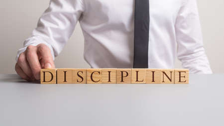 Businessman assembling a discipline sign with wooden blocks. Banque d'images - 122771482