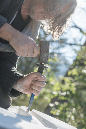 Senior artist using mallet and chisel to carve in stone outside on a sunny day. 版權商用圖片