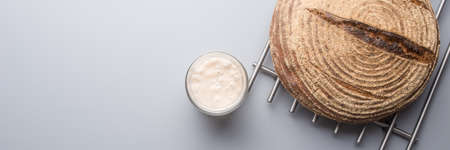 Wide view image of active sourdough yeast in a glass jar and home made bread cooling on a rake over grey background. Stock Photo