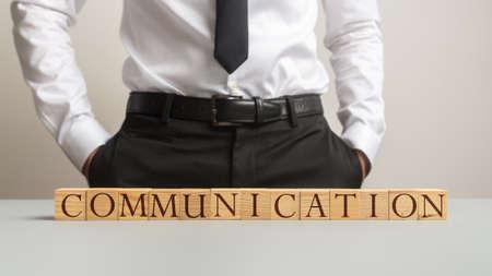 Businessman standing behind an office desk wit a Communication sign made of wooden blocks. Reklamní fotografie