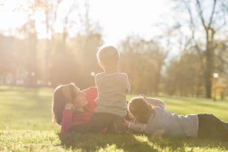 Mother lying in a grass in a park with her three kids around her lit by a bright sun in a conceptual image of family fun and joy.