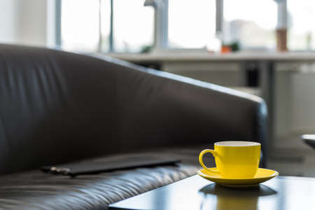 Empty folder on an office couch next to a coffee table with yellow coffee mug.