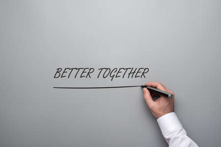 Male hand writing a Better together sign over grey background with black marker.