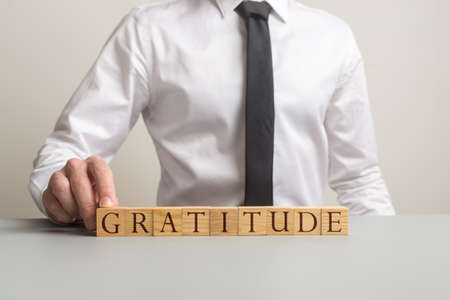 Businessman sitting at his desk assembling a Gratitude sign of wooden cubes in a conceptual image.