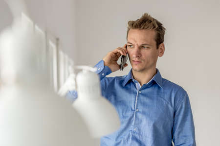 Serious young businessman frowning as he speaks on mobile phone standing in his office.