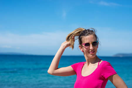 Young woman in pink shirt enjoying holidays at the seaside playing with her hair smiling to the camera.