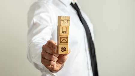 Businessman holding fa stack of our wooden cubes with communication icons on them.
