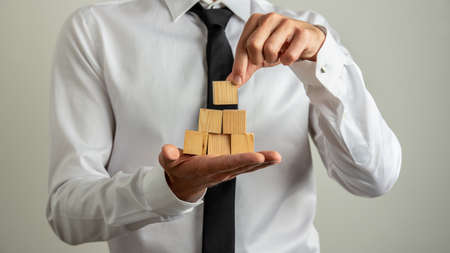 Businessman making a little pyramid of wooden blocks in the palm of his hand.