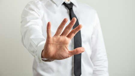 Vorderansicht eines Geschäftsmannes, der mit seiner Hand in Richtung Kamera eine Stoppgeste macht. Standard-Bild