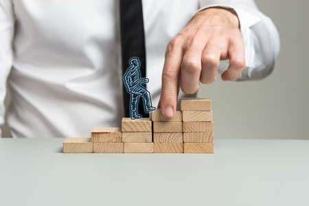 Business executive making wooden steps for a silhouetted businessman to walk upwards in his career. Reklamní fotografie