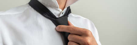 Closeup wide view image of businessman fixing his black tie over grey background.