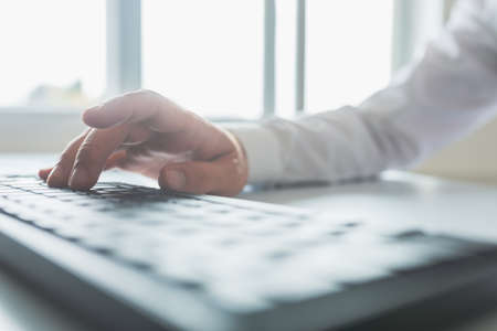 Bright image of a businessman typing on computer keyboard sitting by an office windows. Archivio Fotografico - 126277765