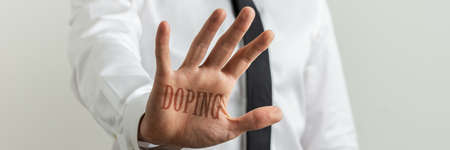 Male hand making a stop sign with a Doping sign over the palm. Archivio Fotografico - 126277771