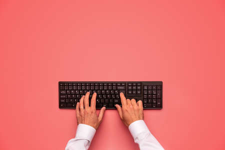 Top view of male hands typing on black computer keyboard. Over pink background. Archivio Fotografico - 126277788