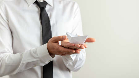 Businessman holding a paper made origami boat in the palm of his hand. Over grey background with copy space on the right side of an image. Archivio Fotografico - 126277789