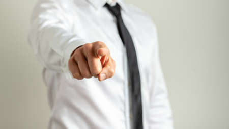 Businessman standing in front of a grey background pointing his finger towards the camera.