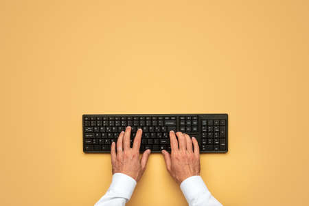 Top view of male hands typing on black computer keyboard over yellow background. Archivio Fotografico - 126277792