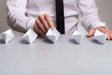 Businessman sitting at his desk with five origami paper boats in front of him.