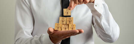 Wide view image of businessman stacking wooden cubes with people icon in a pyramid shape. Archivio Fotografico - 126278803
