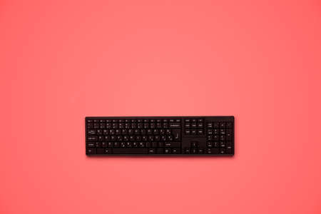 Top view of black computer keyboard. Over bright pink background with copy space.