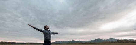 Wide view image of young man celebrating life standing with his arms spread widely under a glorious cloudy sky. Imagens