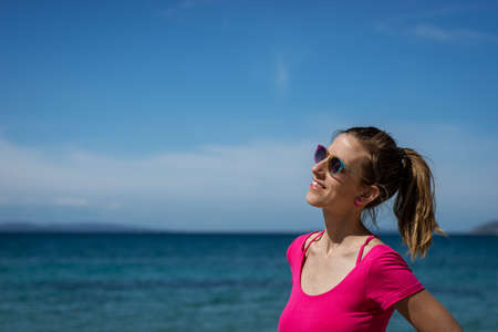 Smiling young woman in pink shirt and colourful sunglasses standing by the sea enjoying and relaxing. 스톡 콘텐츠
