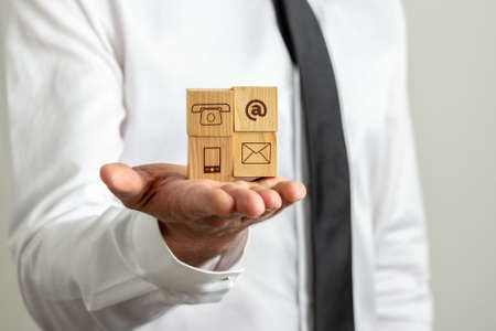 Closeup view of businessman holding four wooden cubes with contact icons in the palm of his hand. Archivio Fotografico - 126278824
