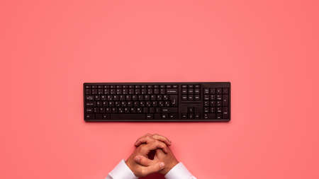 Top view of black computer keyboard with male hands in front of it. Over pink background.