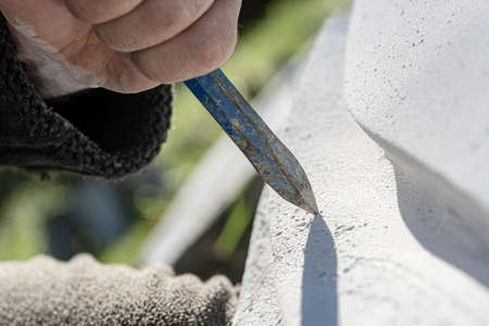 Closeup view of chisel as sculptor works and carves in stone.