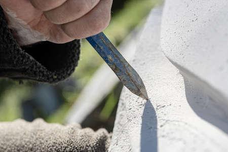 Vue rapprochée du ciseau comme sculpteur travaille et sculpte dans la pierre.