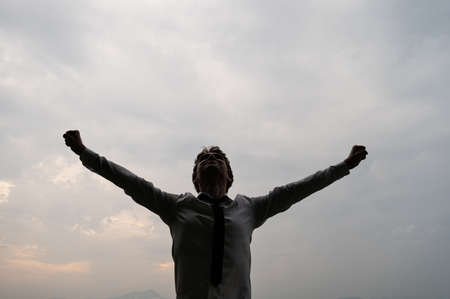 Businessman standing with his arms spread widely making fists under cloudy sky.