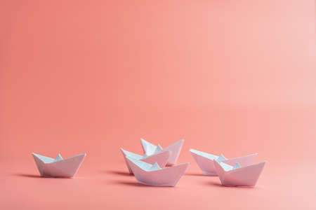 Six origami paper boats over pink background.