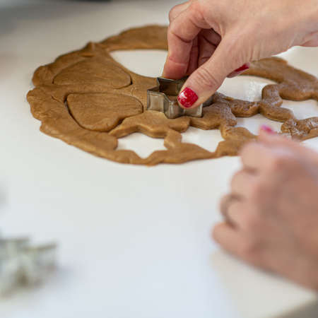 Woman with red painted nails making home made vegan cookies in a shape of a star and heart. Archivio Fotografico - 126278867